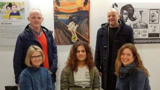 Photo showing Ali Dorani at an exhibition of his work in Norway, surrounded by visitors to the gallery