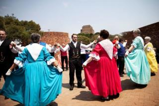 People dressed in traditional Volkspele (a traditional Afrikaner dance) attire, dance at the Voortrekker Monument in Pretoria on Heritage Day on September 24, 2018. - People of Afrikaner descent gathered at the Voortrekker Monument in Pretoria on September 24, 2018 to celebrate Heritage day.
