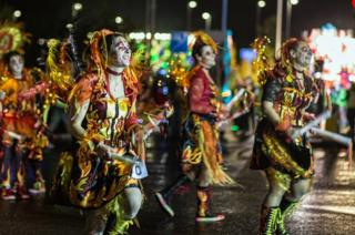 Women dance outside in carnival outfits at Taunton Carnival.
