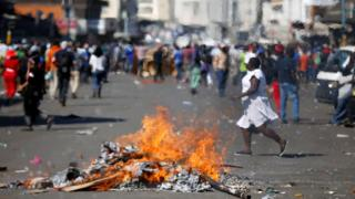 Locals run as supporters of the opposition Movement for Democratic Change (MDC) party of Nelson Chamisa burn barricades in Harare, Zimbabwe, 1 August 2018