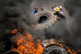 Five men push a giant tyre on to flames
