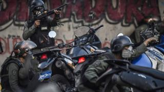 Venezuelan National Guard motorcyclists take cover after coming under fire during a skirmish in Caracas on July 30, 2017