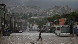 A man walks in a flooded street during the passage of Tropical Storm Laura, in Port-au-Prince, Haiti August 23, 2020.