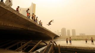 Children at a bridge, one child jumps