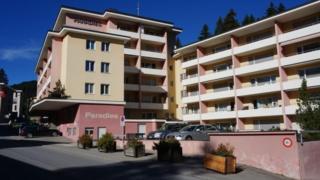 Vista de la fachada del hotel. Son dos torres, una tiene seis pisos y la otra cinco. Está pintando en rosa y amarillo pastel.