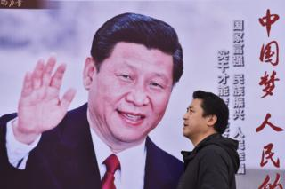 "A man walks past a poster featuring Chinese President Xi Jinping with a slogan reading ""Chinese Dream, People""s Dream"" beside a road in Beijing on 16 October 2017"