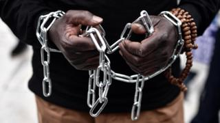 An African migrant with his hands chained, takes part in a march towards the offices of the European Union during a demonstration on December 2, 2017 in central Athens, protesting against the slavery of migrants in Libya.