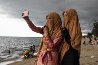 Thai women take a selfie on the Talo Kapo beach