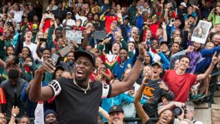 Retired Jamaican Olympic and World champion sprinter Usain Bolt poses for a selfie with spectators as he arrives for the PUMA School of Speed Athletic event at the Ruimsig Stadium in Roodepoort, Johannesburg, on January 29, 2018