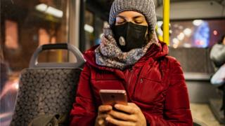 Woman wearing a mask on a bus in winter