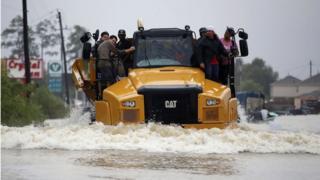 Varias personas huyen de las inundaciones aferrados a un camión en Houston.