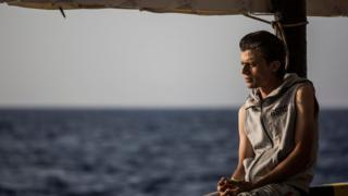 A migrant looks at the sea from the deck of the boat of the NGO Proactiva Open Arms on July 1, 2018.