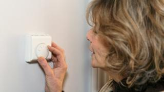 woman adjusts thermostat