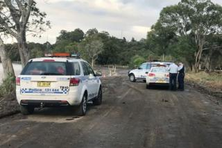 Police guard the site where a car left the road and entered the Tweed River.