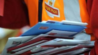 Un agent de Royal Mail avec en main des lettres à déposer (illustration)