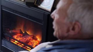 Elderly man in front of fire