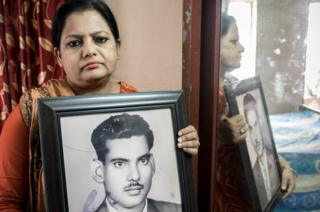 Suraya Parveen with a photo of her father Mejbah Uddin Ahmed