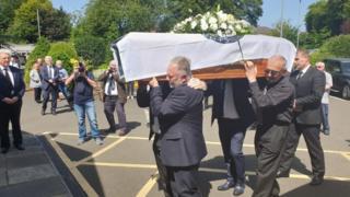 Men carry Ivan Cooper's coffin into St Peter's Church