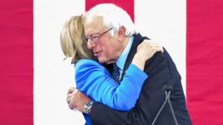 壇上で抱き合うサンダース氏(右)とクリントン氏