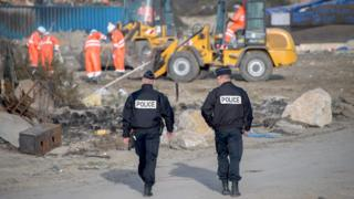 Two police officers walk towards a demolition crew on the site of the former camp at Calais