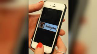Woman holding phone displaying Instagram logo