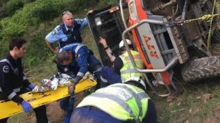 Emergency workers rescue woman trapped under a farm vehicle