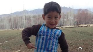 Photo of Murtaza Ahmadi wearing a plastic carrier bag with blue and white stripes. 'Messi' and the number '10' is written in marker
