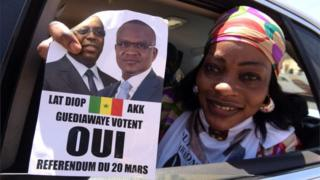 "A woman in a car holds a ""yes"" sign on 12 March, 2016 in Guediawaye suburb in Dakar, during the campaign for referendum on revising Senegal""s constitution, including reducing the presidential mandate from seven to five years."
