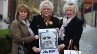 John McKerr's three daughters Agnes, Anne and Mo holding a photograph of their father