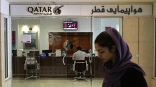 An Iranian woman walks past a Qatar Airways office in Tehran on 6 June 2017