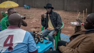 Des hommes en train de boire de la bière dans un bar du camp de réfugiés de Nakivale, dans le sud-ouest de l'Ouganda.