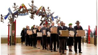 A repatriation team carries remains at a Maori welcome ceremony in 2012