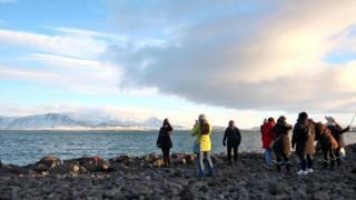 Turistas posam diante de geleira em Reykjavík