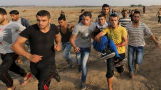 Palestinian protesters carry a man injured in clashes with Israeli troops along the Gaza border fence (20 October 2015)