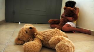 Foto ilustrativa sobre abuso infantil - menina sentada em casa com ursinho de pelúcia