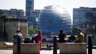 People are seen relaxing in front of City Hall in London, following the outbreak of the coronavirus disease