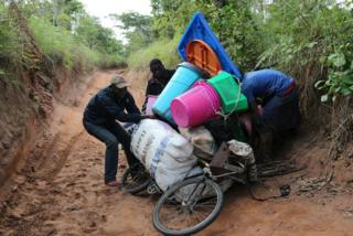 Congolese migrants expelled from Angola attempt to push a rented bicycle to transport their belongings along the dirt road to Tshikapa, Kasai province near the border with Angola in the Democratic Republic of the Congo, October 12, 2018.