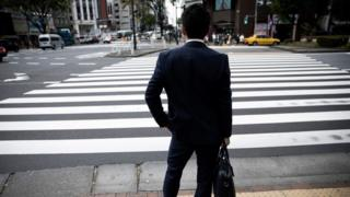 A man stands in front of a street in central Tokyo on April 27, 2017