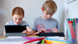 Two UK children doing school work at home