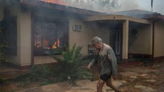 A man walks past a burning house in Coligny that was reportedly set on fire by protesters during clashes that erupted after a court bailed two men accused of killing a boy on May 8, 2017