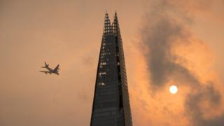 A plane flying past the Shard in London