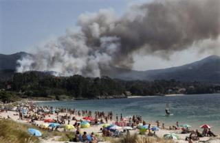 in_pictures Smoke rises from a forest fire near a tourist beach