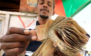 A dealer counts bundles of cash at an open air currency exchange bureau within the Hamarweyne open air market in Mogadishu, Somalia, 5 February 2020