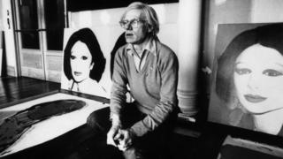 Artist Andy Warhol next to