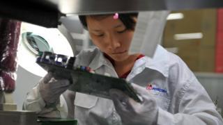 在中國深圳工廠組裝蘋果零件的富士康員工。