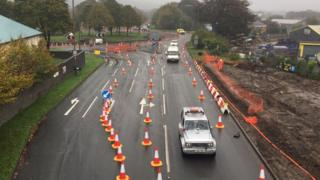 Cars driving through lanes off the roundabout lined with traffic cones.