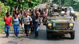 Une patrouille de militaires français passe devant une troupe de Hutus en 1994.