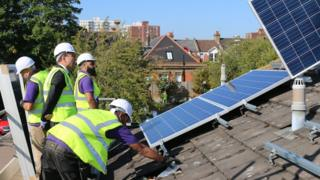 workmen installing solar panels on roof