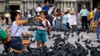 Mulher e criança dando de comer a pombos em uma praça