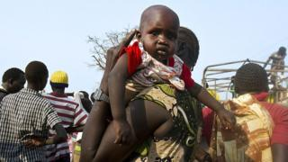 A woman holds a baby as refugees from South Sudan wait to board a truck at Dzaipi Refugee Transit Centre in Adjumani, northern Uganda, to be transferred to nearby Nyumanzi Resettlement Camp